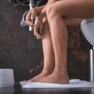 womans legs sat on white toilet next to toilet roll