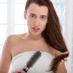 woman holding a hair brush with hair loss