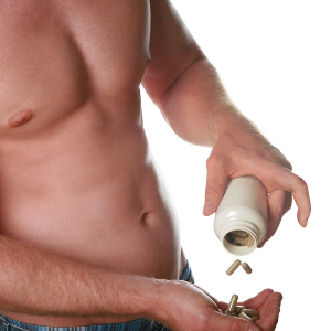 bare chested man empting out a jar of suppliments on the keto diet